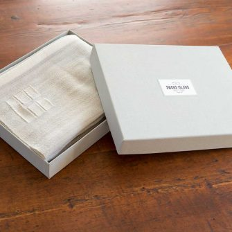 Swans Island handwoven wrap in custom grey linen gift box.