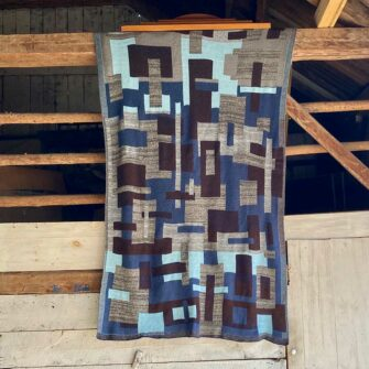 Swans-Island_Artisan-Patchwork-Throw-#4 knit in Navy, Brown, Heathered grays and turquoise