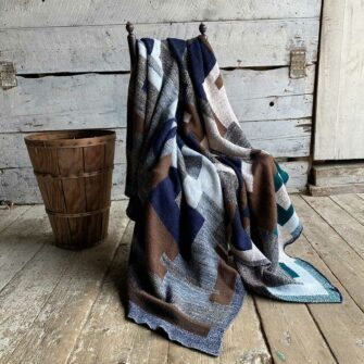 Swans-Island_Artisan-Patchwork-Throw-#5-knit in navy, grays, browns, sand spruce green