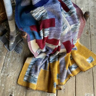 Artisan Patchwork Throw #22 is knit with a background of heathered greys, with patchwork blocks in denim, navy, charcoal, burgundy, and sunflower yellow tones.