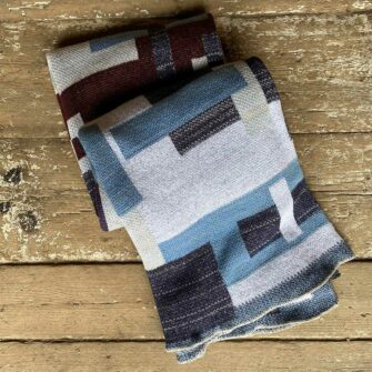 Swans Island Artisan Patchwork Throw #25 - Knit in USA with heathered greys and dark blue tones, with patchwork blocks in sky blue, heathered cream, burgundy, and denim blue tones.