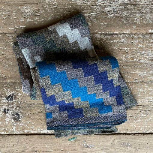 Swans Island Artisan Patchwork Throw #26 knit in USA in soft heathered greys and heathered lichen and brown tones, with patchwork blocks in denim blue, cream, green, brown and azure blue tones.