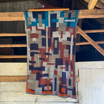 Swans Island Artisan Patchwork Throw #20 knit in shades of heathered grey, navy, russet turq and orange.