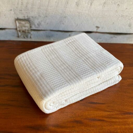 Swans Island Caroline Blanket in undyed natural cotton has a beautiful banded cable texture. Woven in Maine.