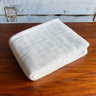Swans Island Dover Blanket in undyed natural cotton has a beautiful basketweave texture, is woven in Maine.
