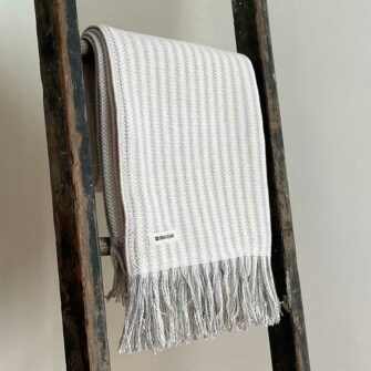 Swans Island's Cotton Ticking Throw Fringe blanket is woven in Maine with 100% American cotton.