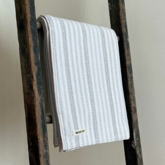Swans Island's Cotton Ticking Throw blanket is woven in Maine with 100% American cotton.